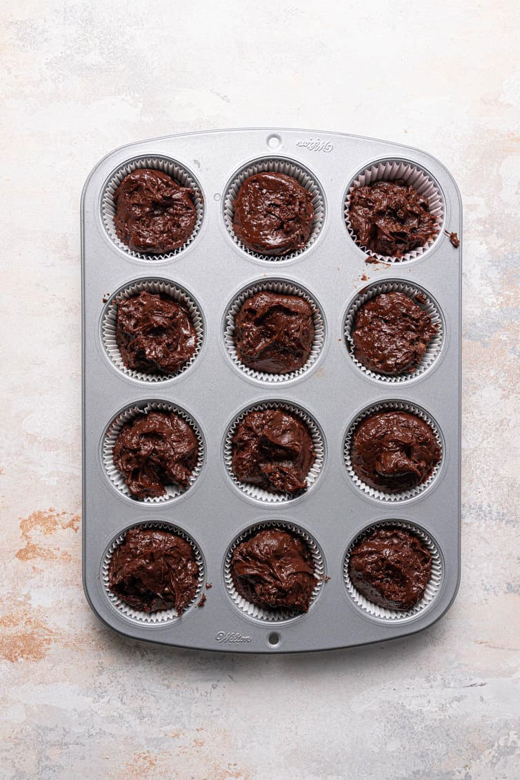 Chocolate muffin batter portioned into a muffin cup.