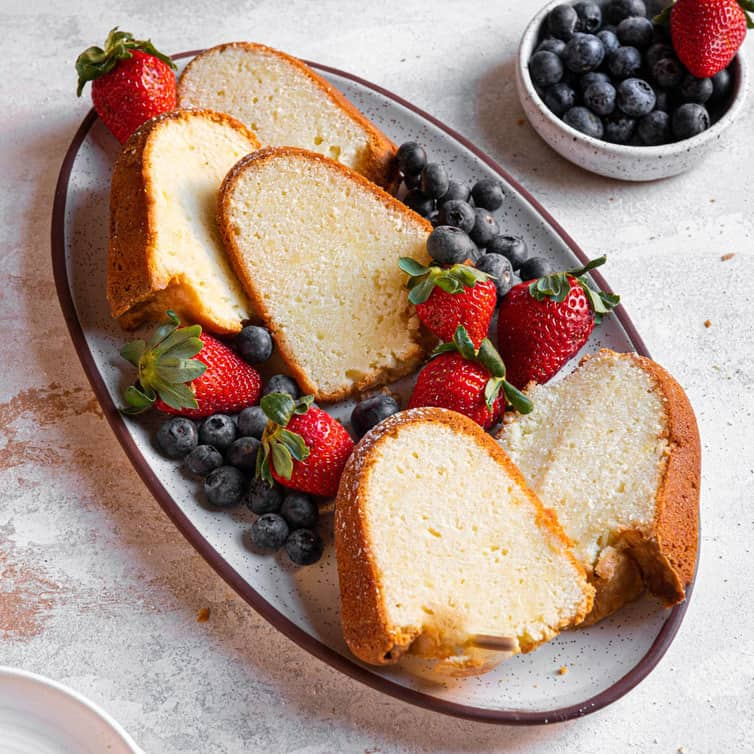 Slices of cream cheese pound cake on a platter with strawberries and blueberries.