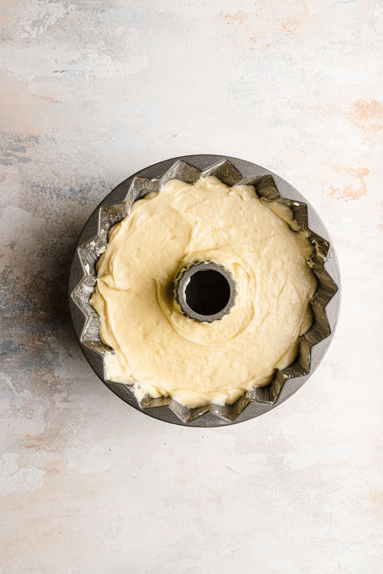 Cream cheese pound cake batter spread in a Bundt pan.