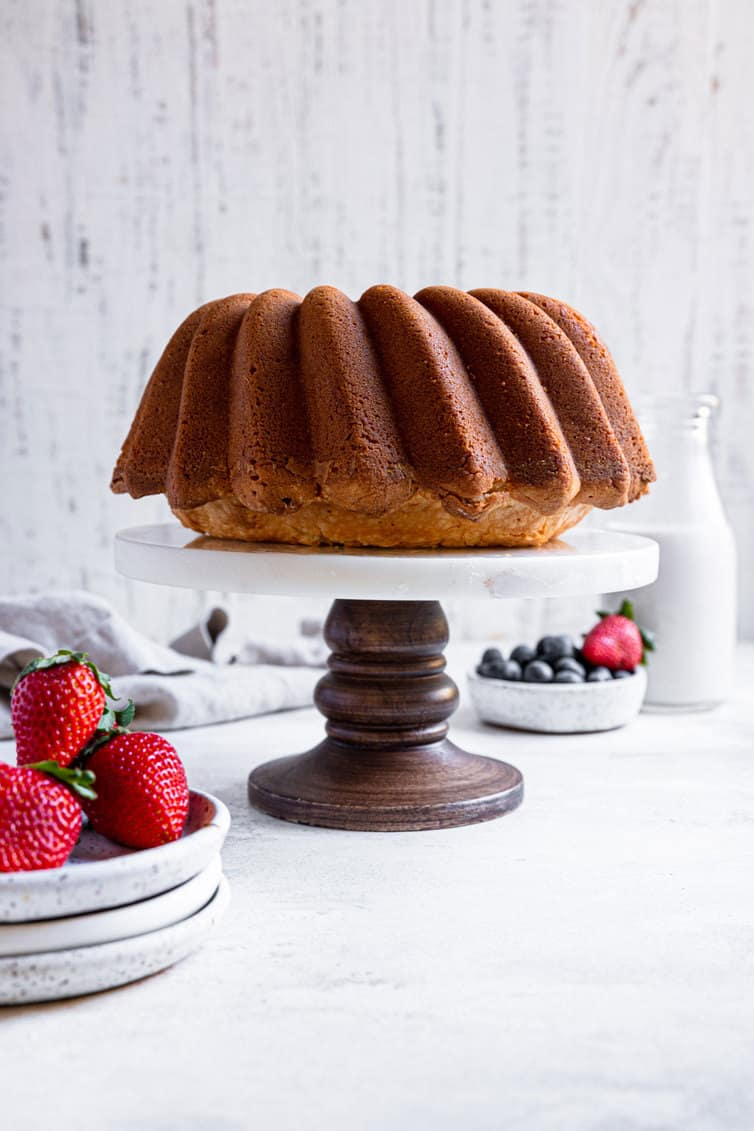 Cream cheese pound cake on a pedestal stand with strawberries in a bowl.