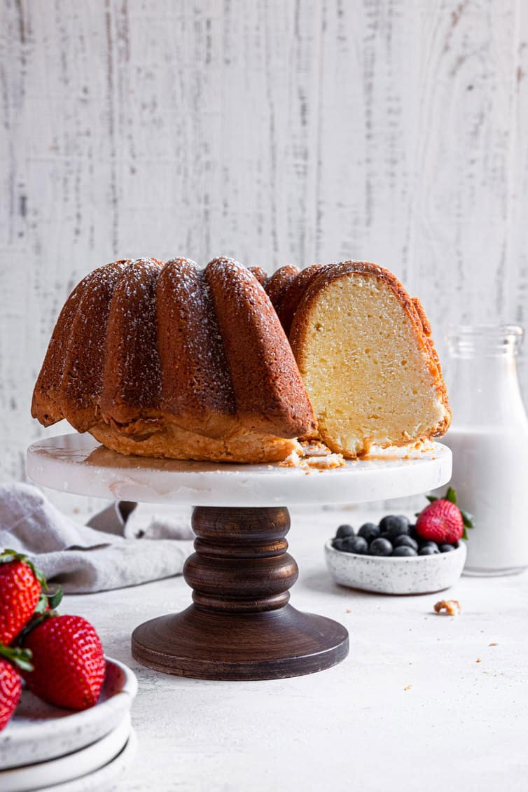 Cream cheese pound cake on a stand with slices removed.