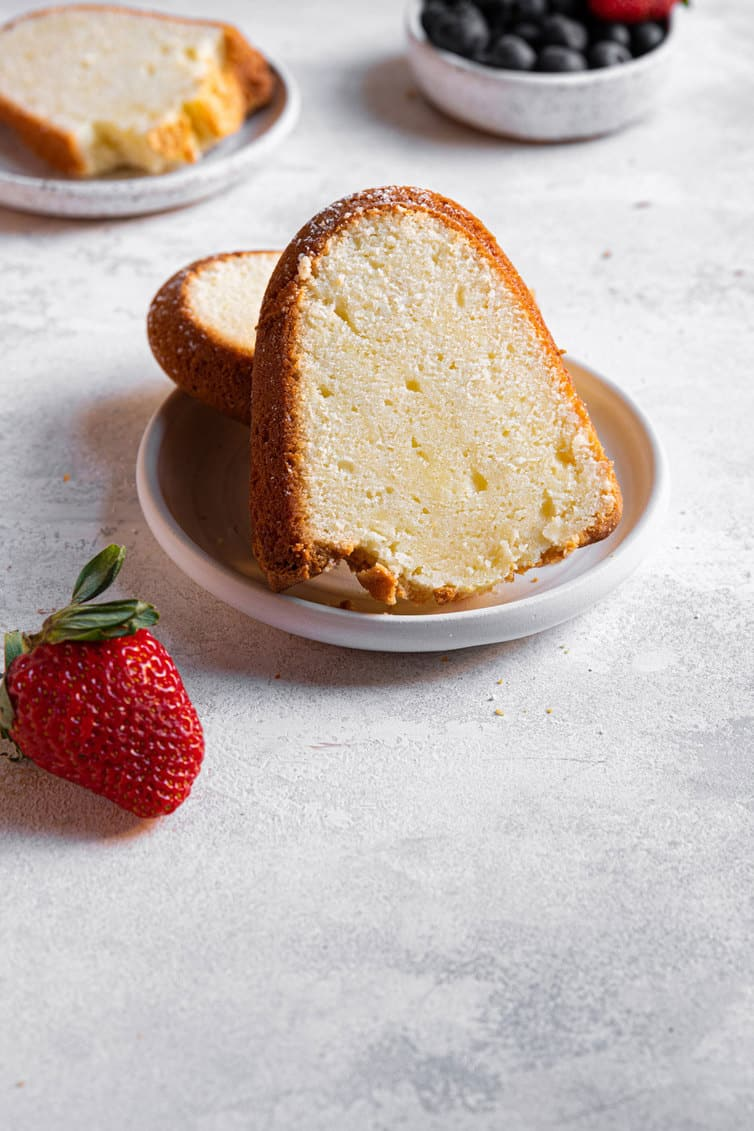 A slice of cream cheese pound cake on a plate with a strawberry next to it.