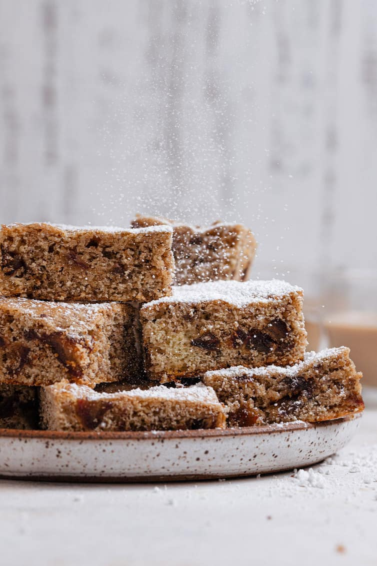 Date bars stacked on a plate and sprinkled with powdered sugar.