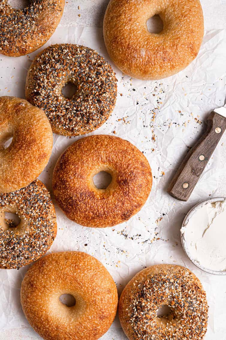 Homemade bagels on a counter with a knife and cream cheese.