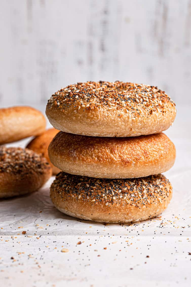 Stack of three bagels on a counter.