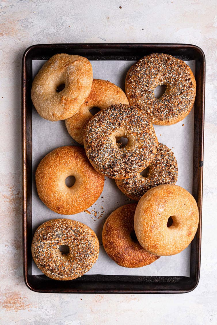 Plain and everything bagels on a baking sheet lined with parchment paper.