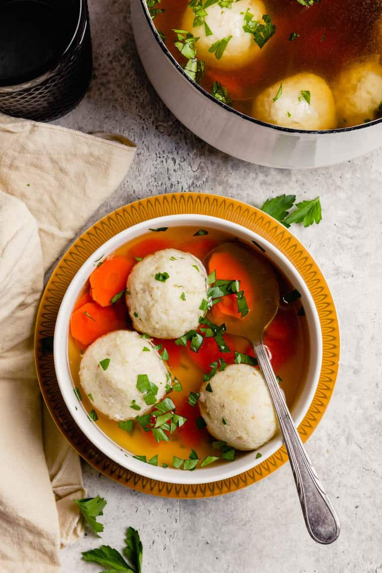 Uma tigela de sopa de matzo ball com uma colher e uma panela de sopa de matzo ball nas costas.