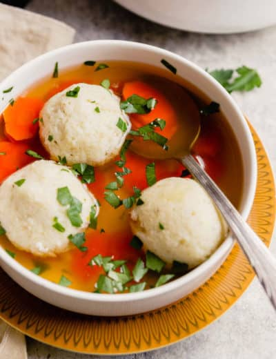 A warm bowl of matzo ball soup on a yellow plate with a silver spoon in the bowl topped with parsley.