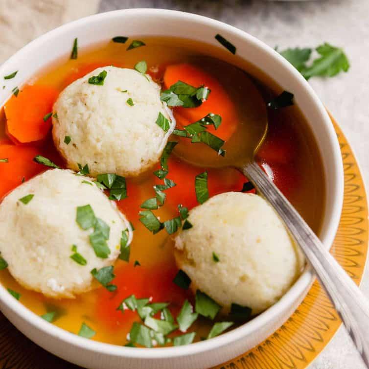 Sopa de pão ázimo caseiro em uma tigela branca com três bolas de pão ázimo cozidas por cima e uma colher de prata na tigela.