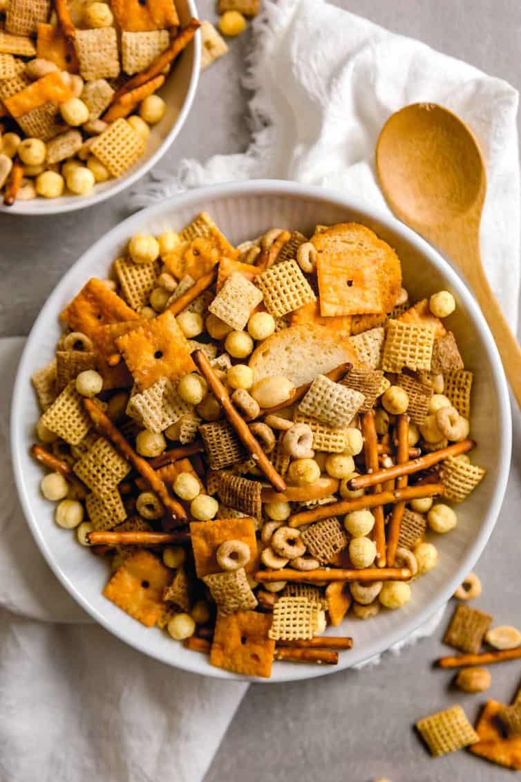 A bowl of nuts and bolts snack mix with wooden spoon.