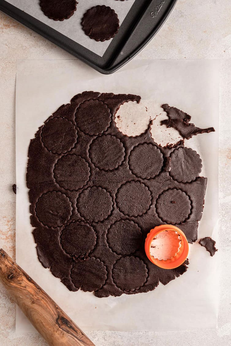 Cutting out circles from chocolate cookie dough.