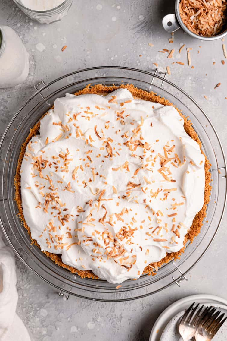 A full coconut cream pie looking top down on a cooling rack topped with shredded coconut.