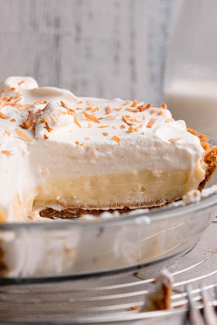 A glass pie plate with coconut cream pie missing a slice so you can see the layers of crust, coconut filling, and whipped cream.