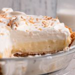 A square picture of fresh coconut pie in a glass pie plate showing the layers of graham cracker crust, coconut filling, and a whipped topping with toasted shredded coconut.