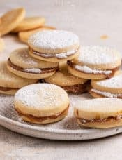 A square picture with a stack of alfajores on a white plate dusted with powdered sugar.