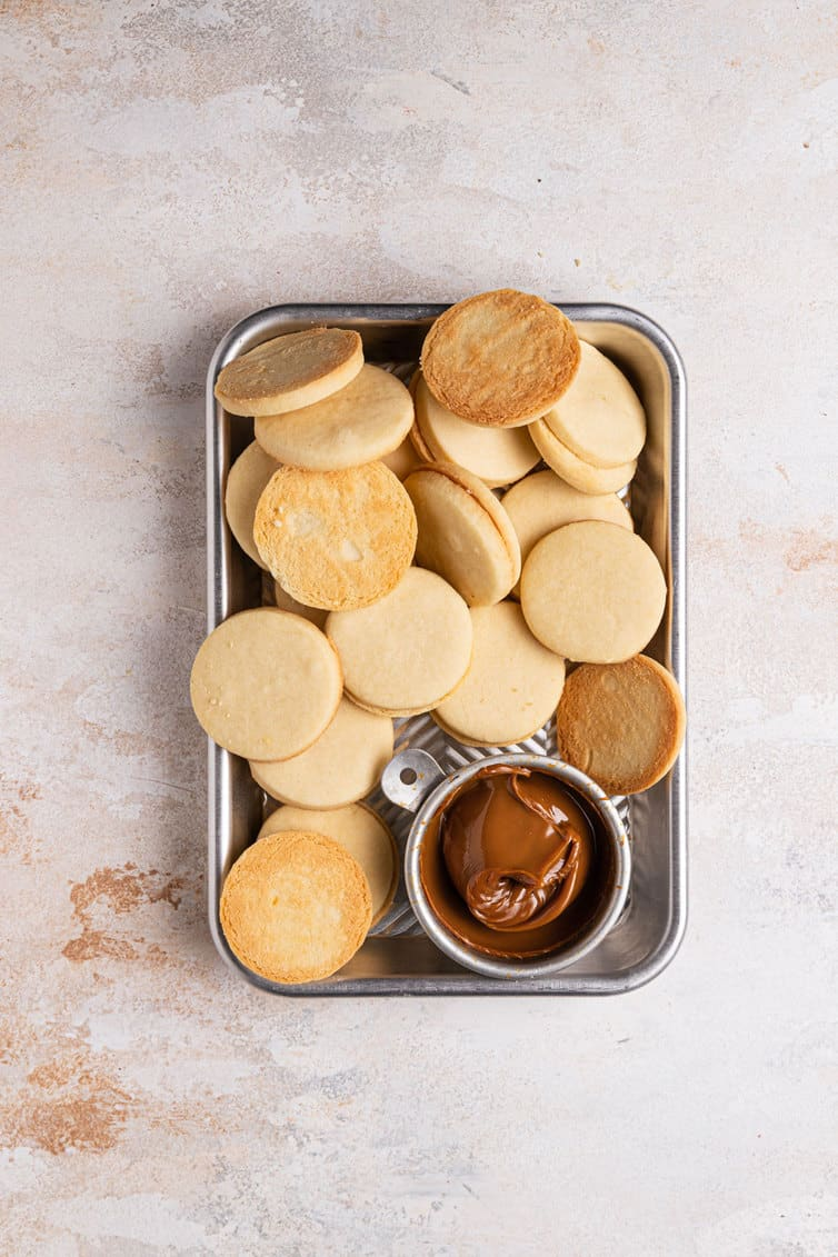 A sliver pan with a small cup of dulce de leche in the bottom right with fresh baked shortbread cookies covering the rest of the tray.