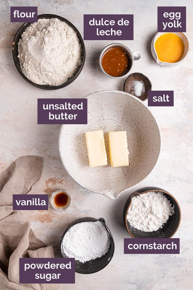 The ingredients for alfajores labeled on a white counter.