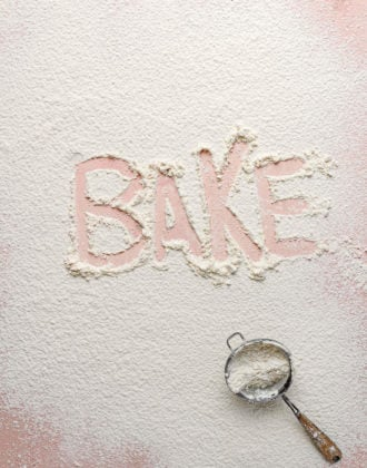 """Flour dusted on a counter with the word """"bake"""" traced in it."""