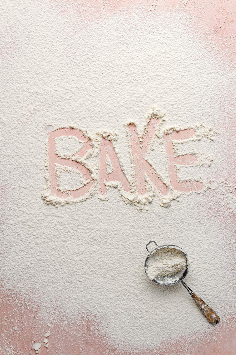"Flour dusted on a counter with the word ""bake"" traced in it."