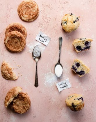 Snickerdoodle cookies and blueberry muffins with spoonfuls of baking soda and baking powder next to them.