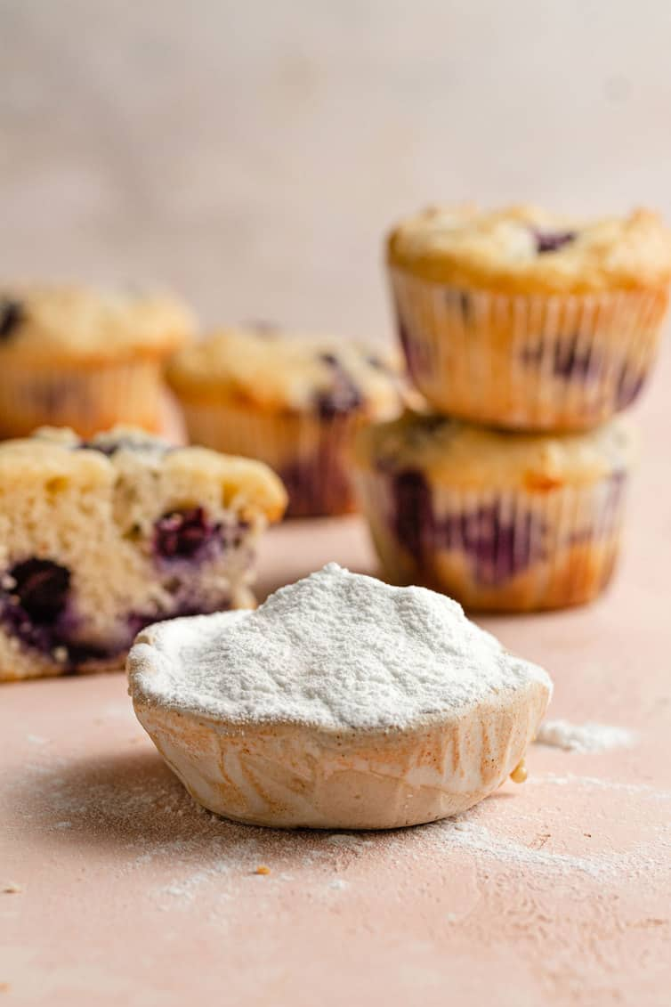 A scoop of baking powder in front of blueberry muffins.