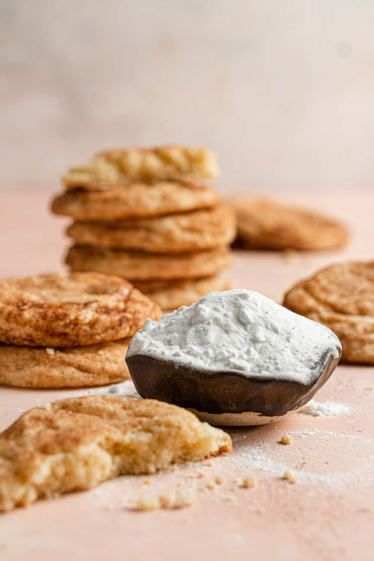 A scoop of baking soda surrounded by snickerdoodle cookies.