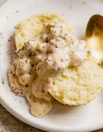 A biscuit topped with sausage gravy on a white plate with a gold spoon on the right.