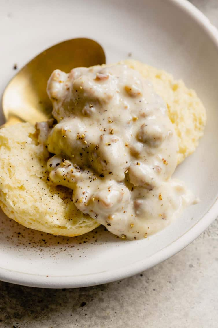 A close up shot of sausage gravy on top of an open biscuit on a white plate.