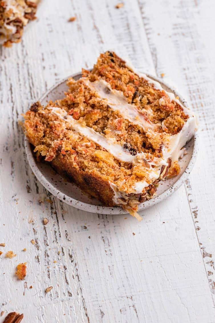 Fatia de bolo de cenoura de lado em um prato.