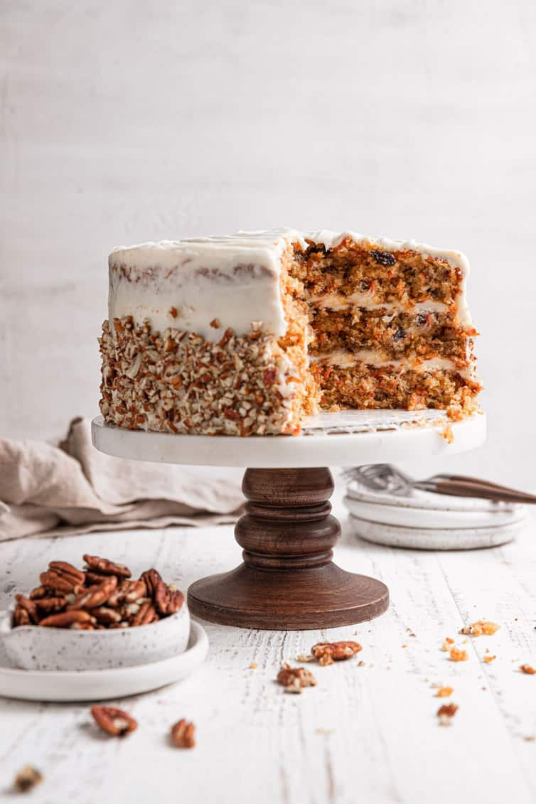 Carrot cake on a cake pedestal, showing the inside of the cake.