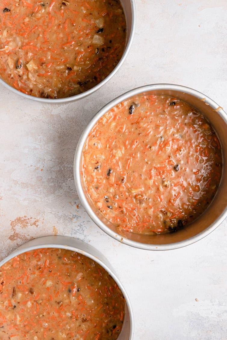 Carrot cake batter in three round cake pans.