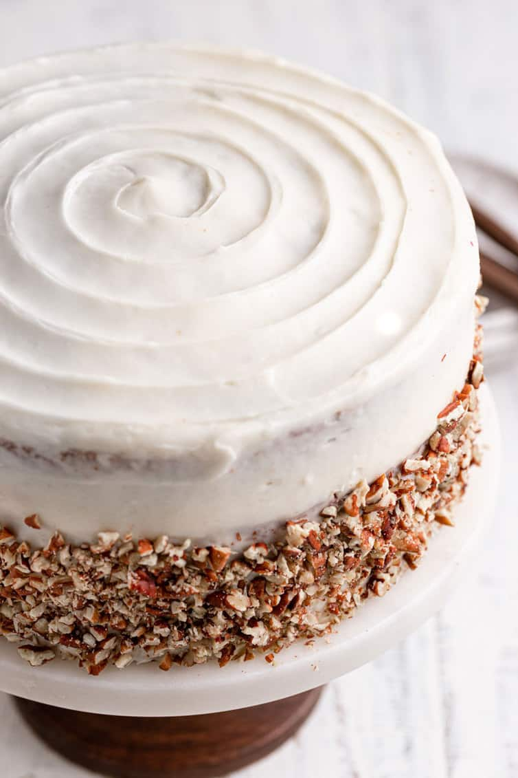 Fully assembled carrot cake with spiral icing design on top and pecans pressed into sides.