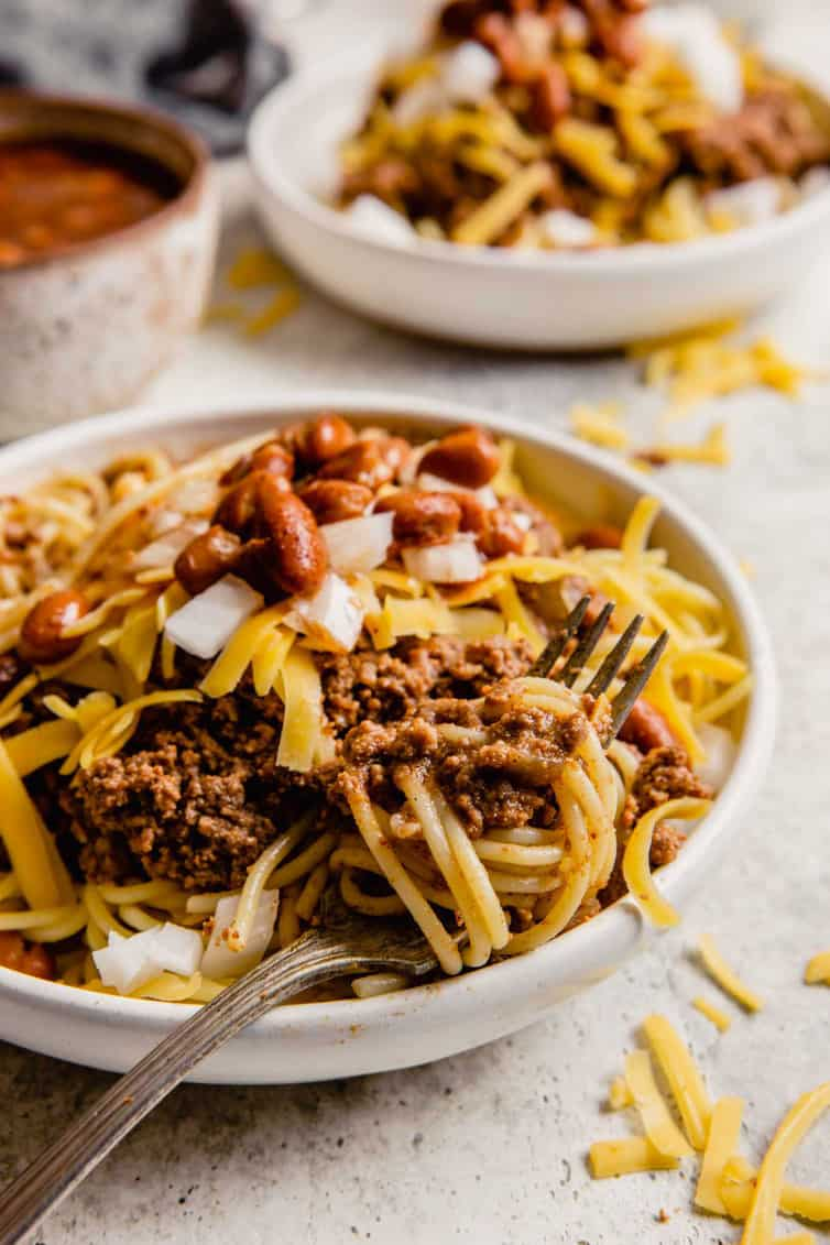 A fork twirling together spaghetti noodles with Cincinnati chili.