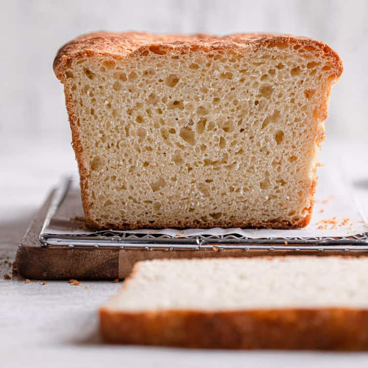 An English muffin bread loaf sliced to show the nooks and crannies of the bread.