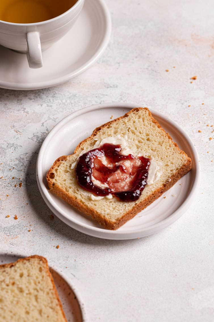 A slice of English muffin bread with butter and jam in front of a mug of tea.