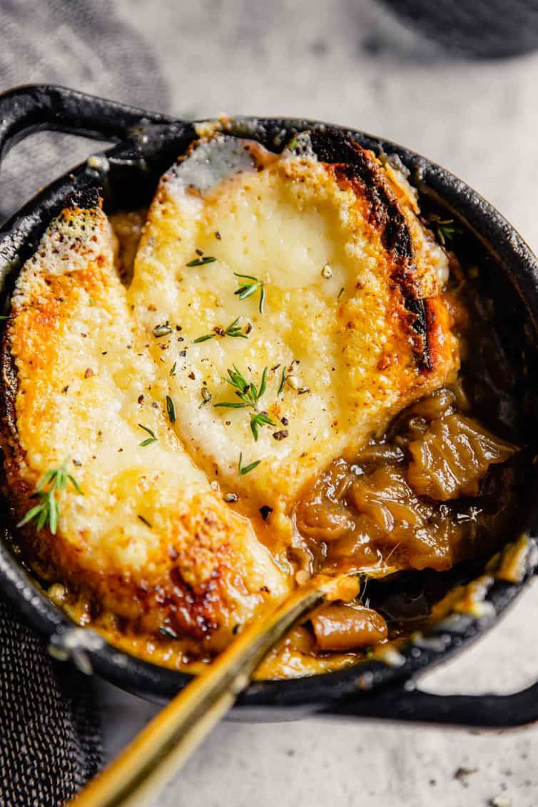 A bowl of French onion soup with a spoon scooping out onions.