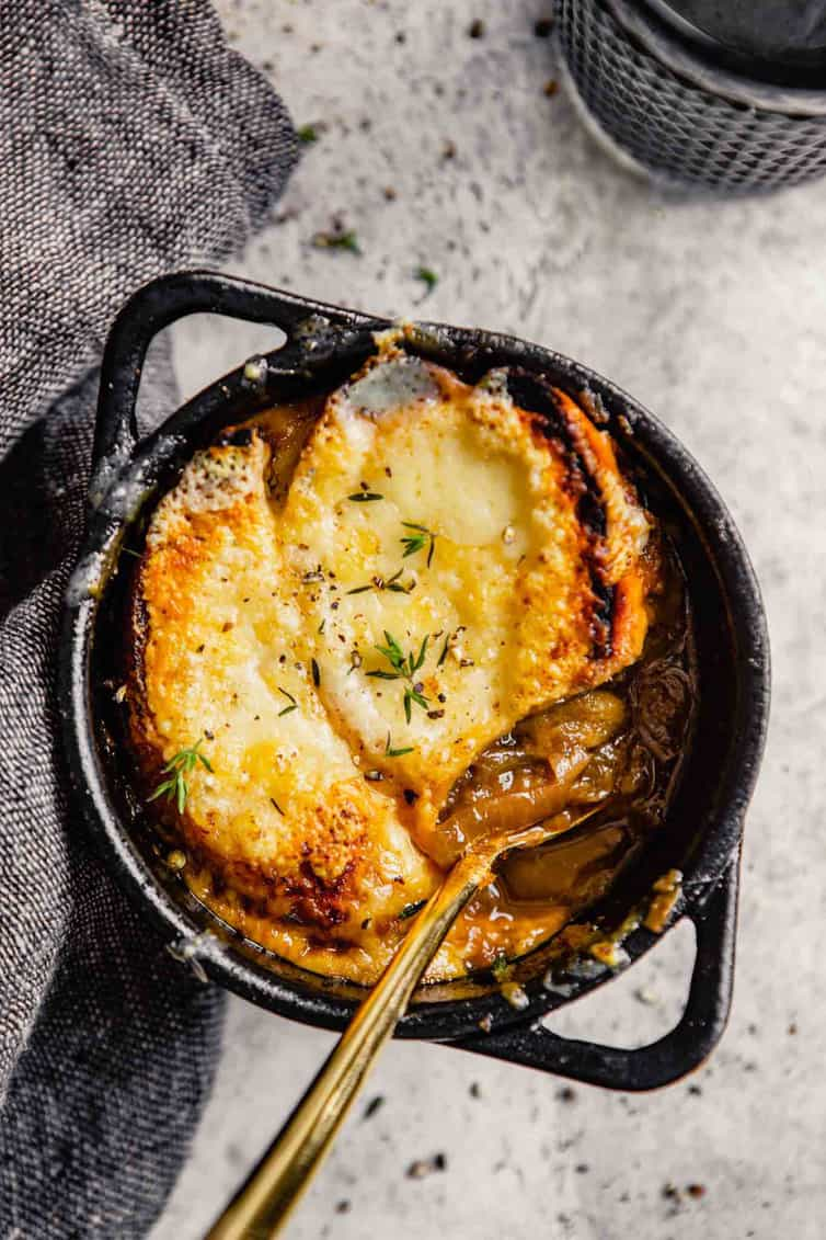 A bowl of French Onion Soup with a spoon inside.