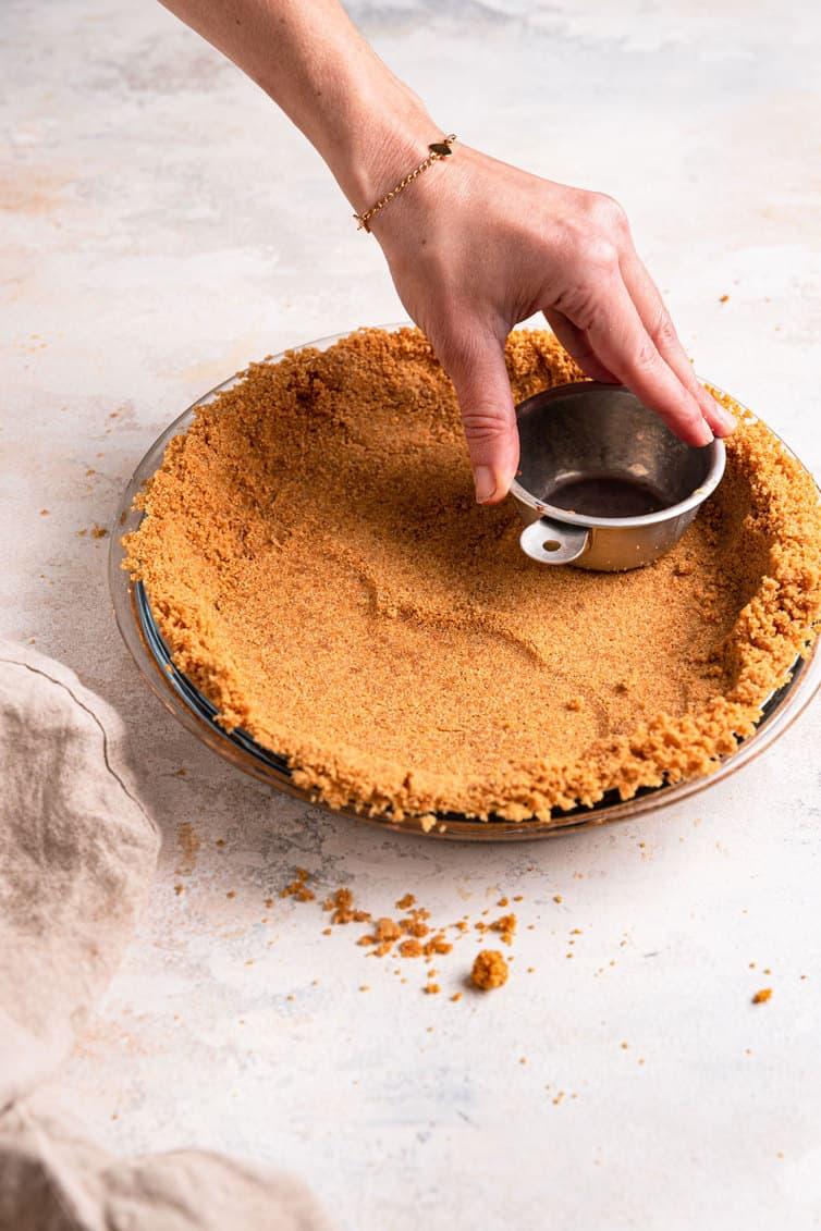 Graham cracker crust being packed into a pie plate using a measuring cup.