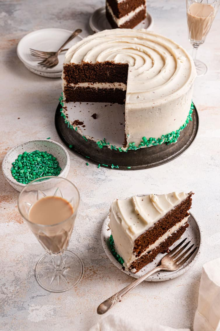 A slice of guinness chocolate cake on a plate with a fork in front of a full cake on a silver stand.