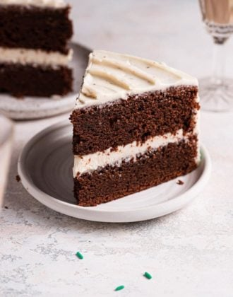 A slice of Guinness chocolate cake on a white plate with a second slice behind.