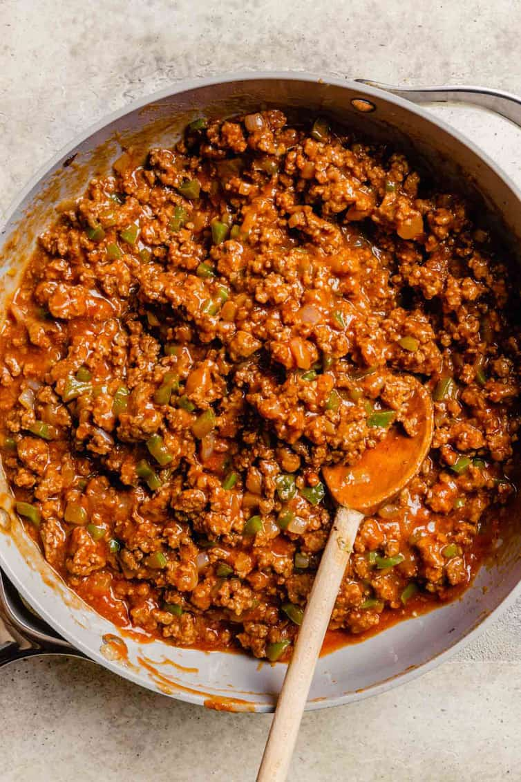 Homemade sloppy joe meat in a skillet with a wooden spoon.