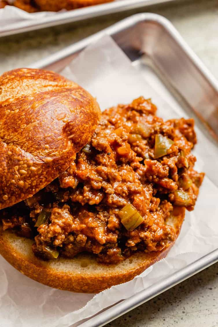 From the front, a metal tray lined with parchment paper with a sloppy joe sandwich on top.