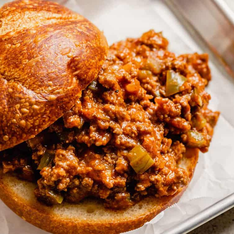 A square photo from the front of a sloppy joe sandwich with the top of the bun slid back to show the sloppy joe meat.