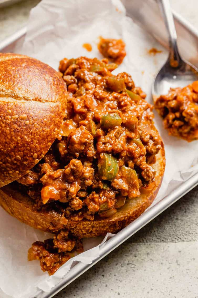 Homemade sloppy joes with the bun top pulled back and a spoon of sloppy joe meat to the right.