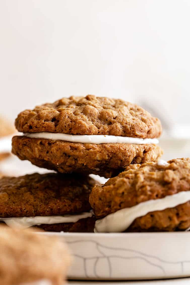Three oatmeal cream pies on a white plate stacked with two on bottom and one on top.