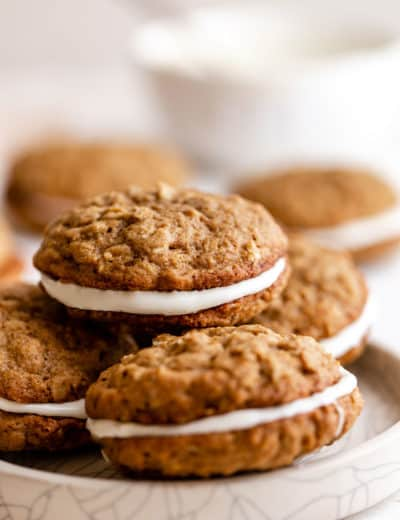 A stack of oatmeal cream pies on a white plate with a white bowl in the back right.