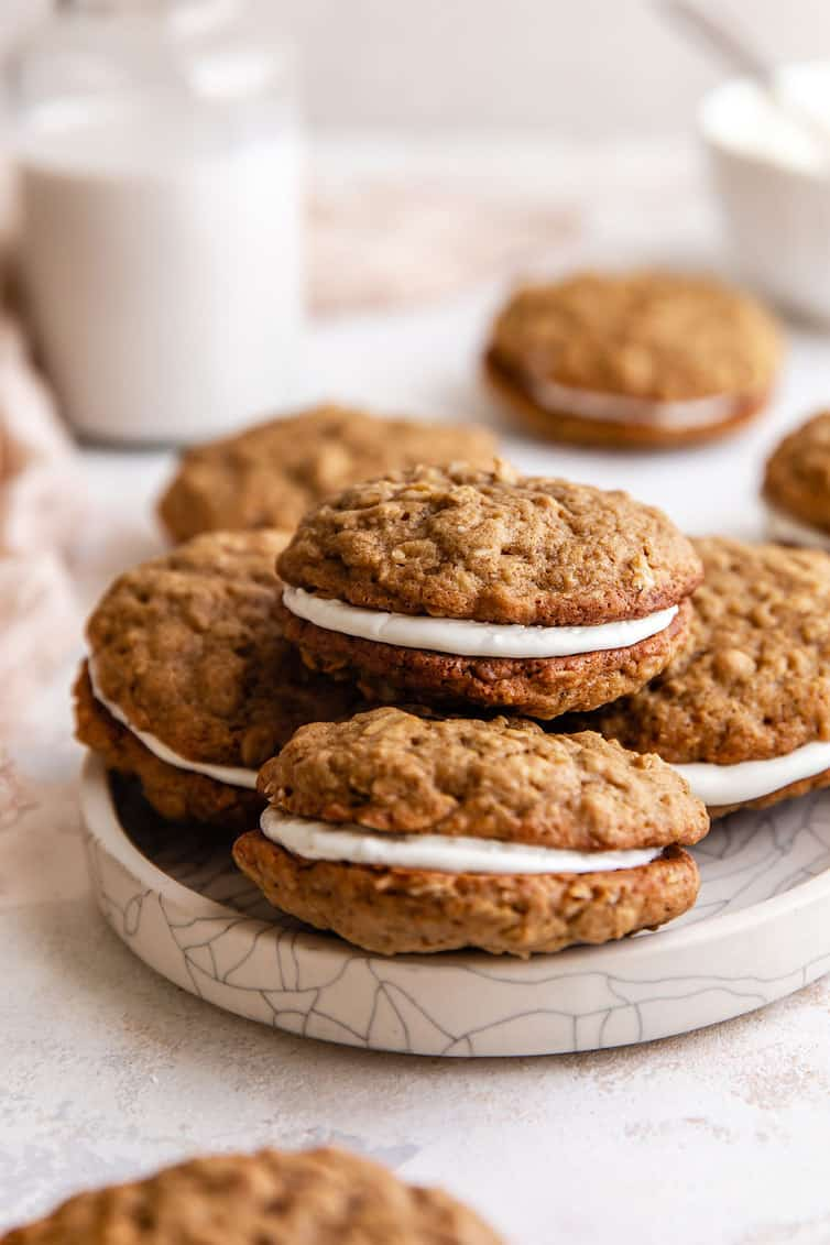 A stack of four oatmeal cream pies on a white plate with a glass of milk in the back left.