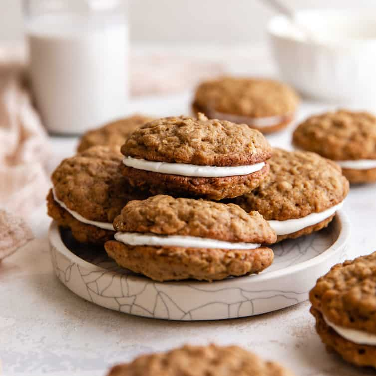 A square picture with a white plate piled up with 4 oatmeal cream pies.