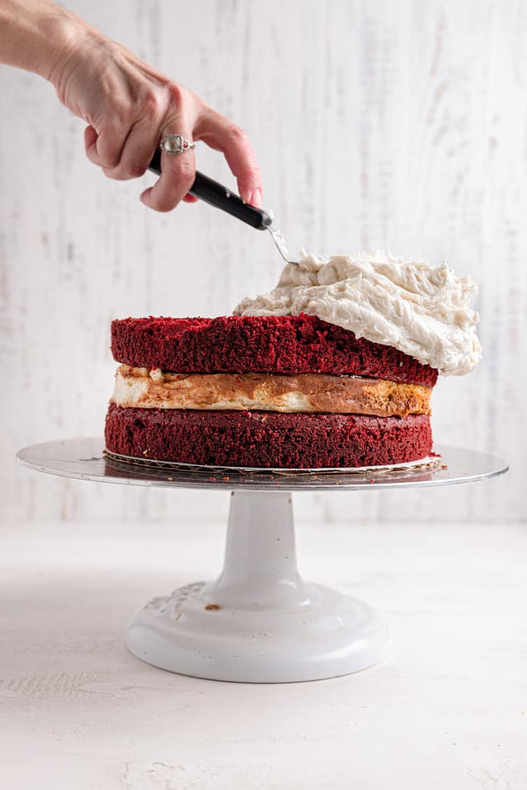A hand holding an offset spatula spreads cream cheese frosting on a red velvet cheesecake.