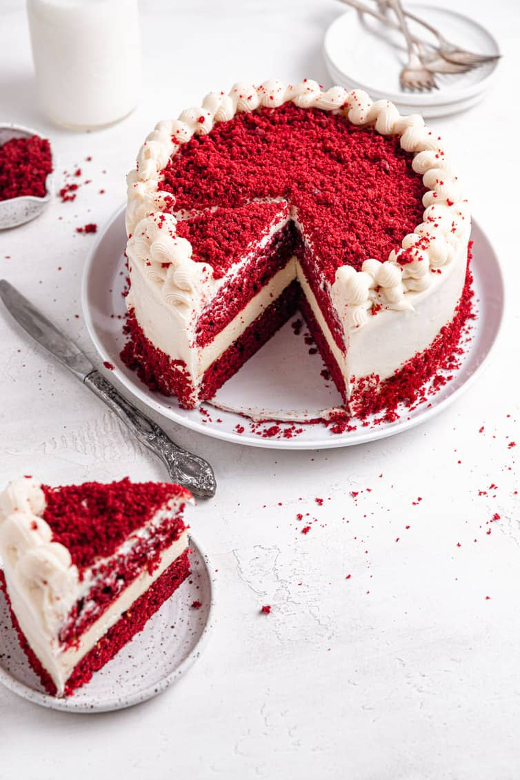 A red velvet cheesecake with a slice on a small white plate in front of the rest of the cake on a large white plate in the back.